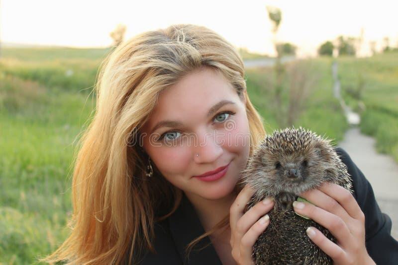 Menina que guarda um ouriço imagens de stock