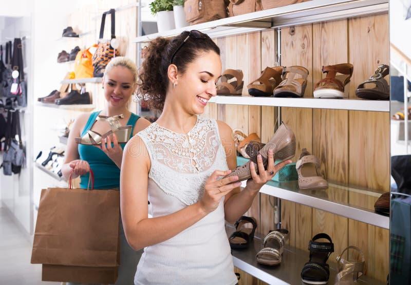 Menina que guarda um par de sapatas escolhido no boutique fotografia de stock royalty free