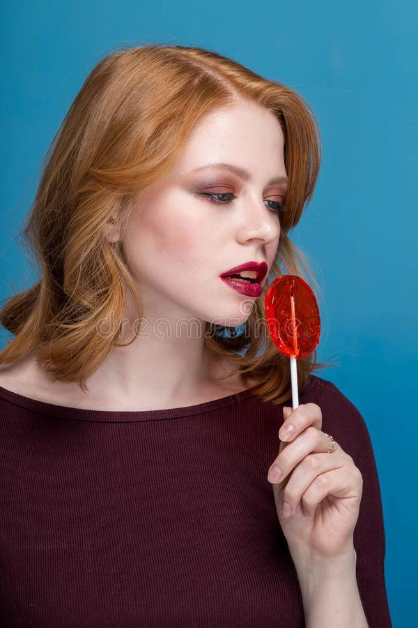A menina que guarda um pirulito vermelho Rosa vermelha anunciar Menina que guarda um pirulito em sua boca imagem de stock