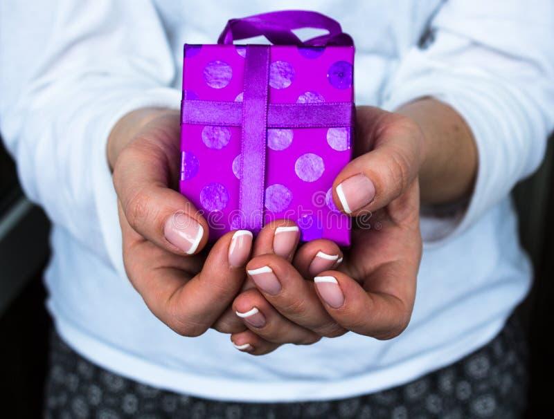 Menina que guarda um presente em suas mãos imagem de stock