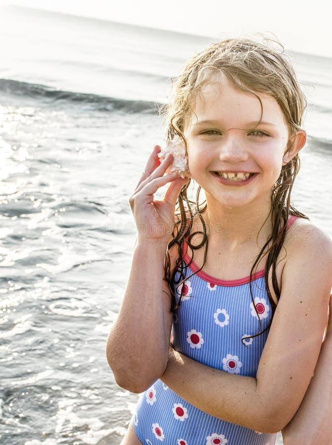 Menina que guarda um shell a sua orelha fotos de stock royalty free