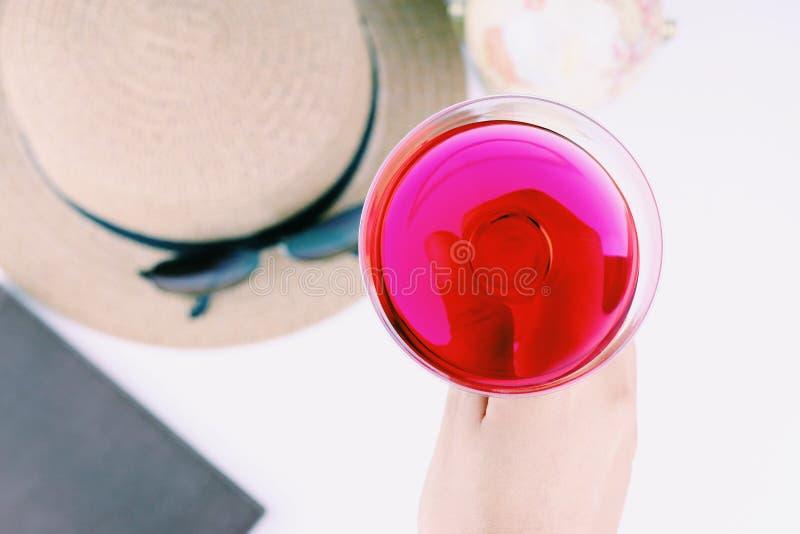 Menina que guarda um vidro do cocktail vermelho com chapéu, bola global foto de stock