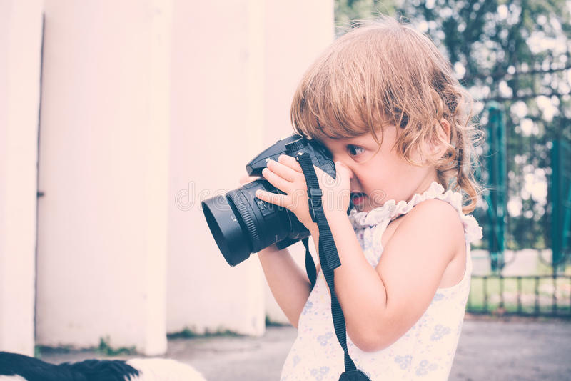 Menina que guarda uma câmera e que toma imagens imagens de stock royalty free