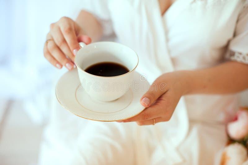 Menina que guarda uma caneca de caf? branco Em um revestimento branco foto de stock royalty free