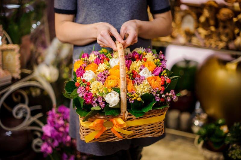 A menina que guarda uma cesta bonita da multi mola colorida floresce fotografia de stock