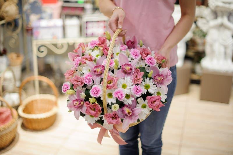 Menina que guarda uma cesta bonita de orquídeas cor-de-rosa e dos camomiles brancos foto de stock