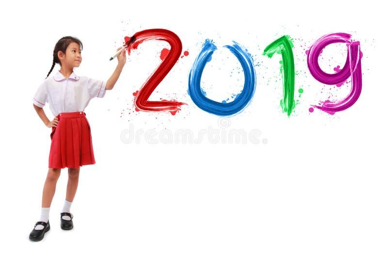Menina que guarda uma escova de pintura que pinta o ano novo feliz 2019 foto de stock royalty free