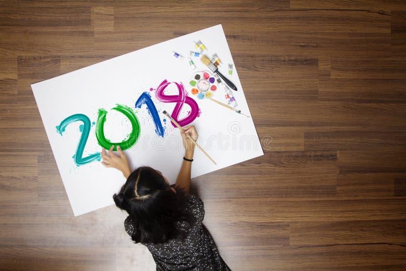 Menina que guarda uma escova de pintura que pinta o ano novo feliz 2018 fotos de stock royalty free