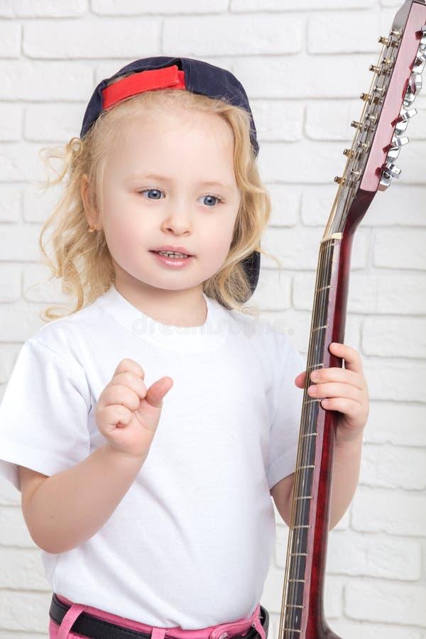 Menina que guarda uma guitarra imagens de stock royalty free