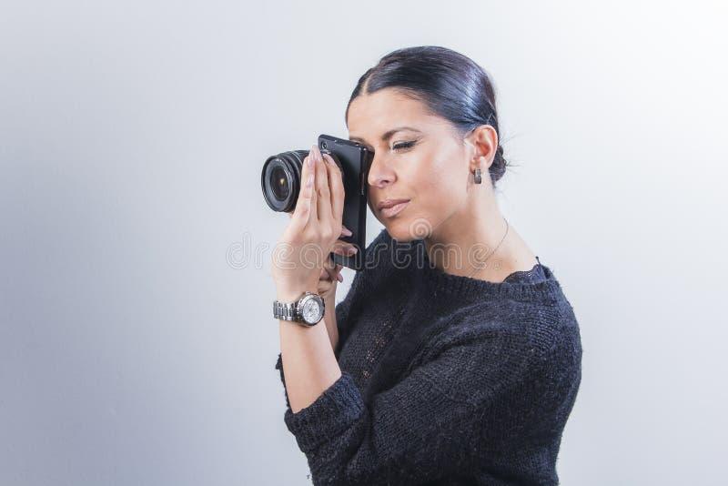 Menina que guarda uma lente ao lado de uma câmera do smartphone fotografia de stock