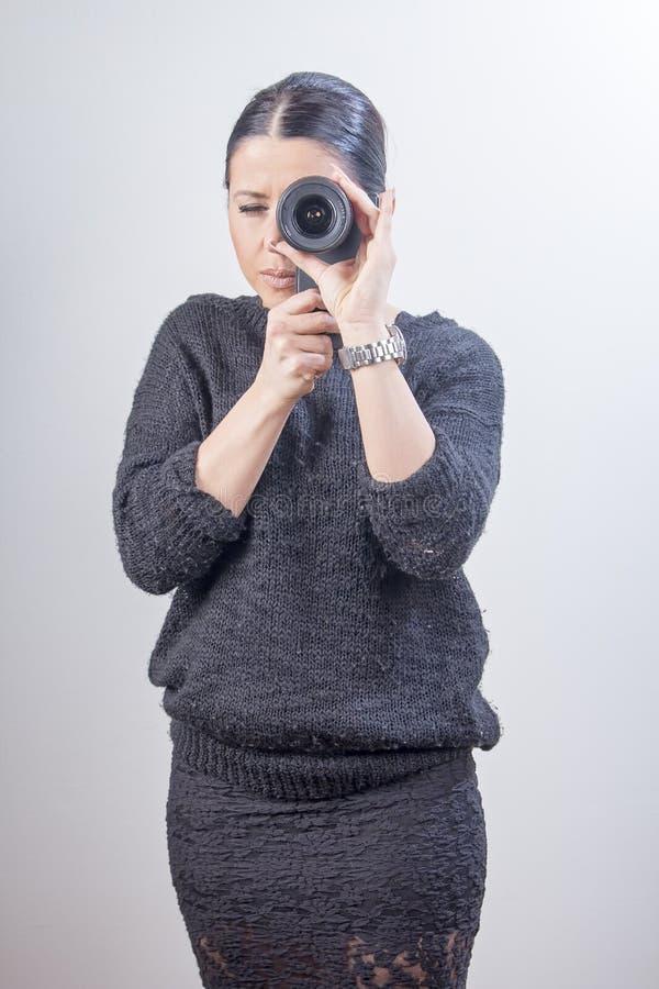 Menina que guarda uma lente ao lado de uma câmera do smartphone fotos de stock