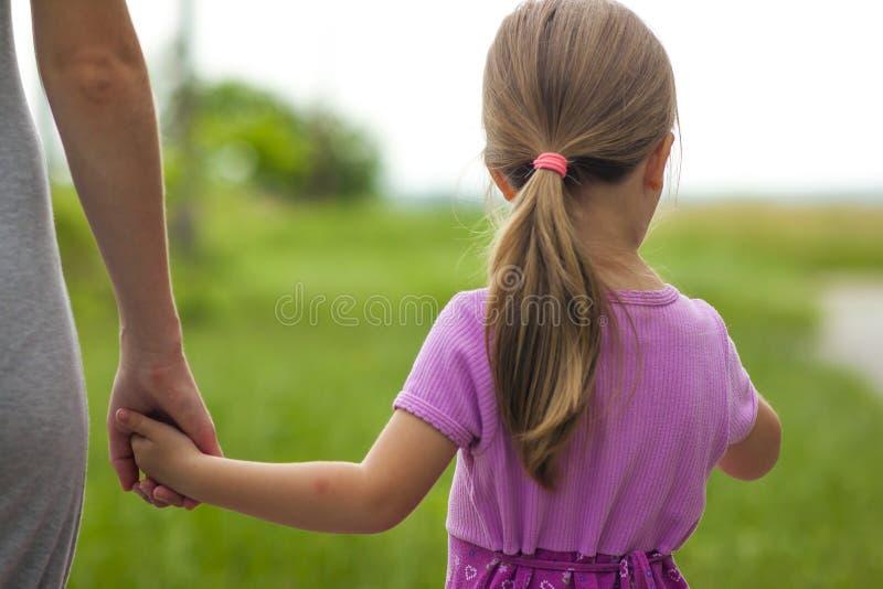 Menina que guarda uma mão de sua mãe Conce das relações de família fotografia de stock royalty free