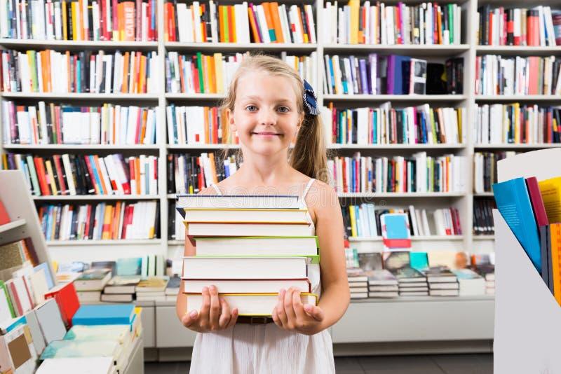 Menina que guarda uma pilha de livros em uma livraria fotos de stock