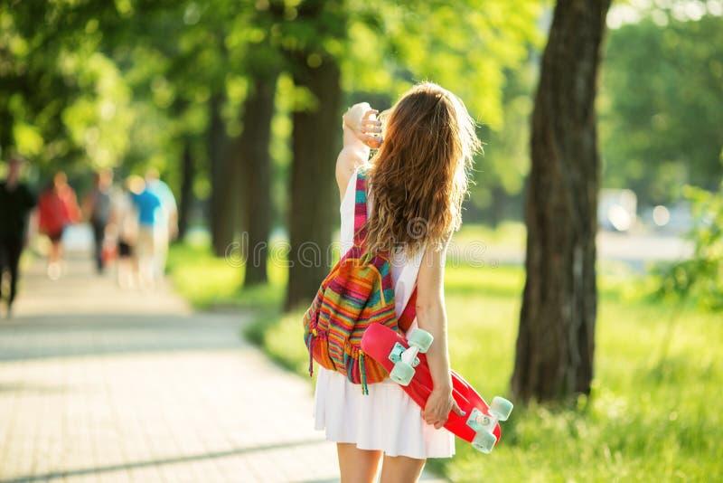Menina que guarda uma placa plástica do patim fora foto de stock royalty free
