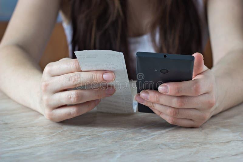 Menina que guarda uma verificação em seus mão e telefone, contando as despesas, financeiras foto de stock