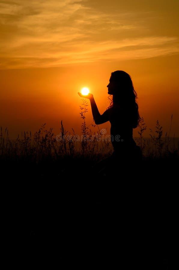 Menina que guardara o sol em sua palma imagens de stock