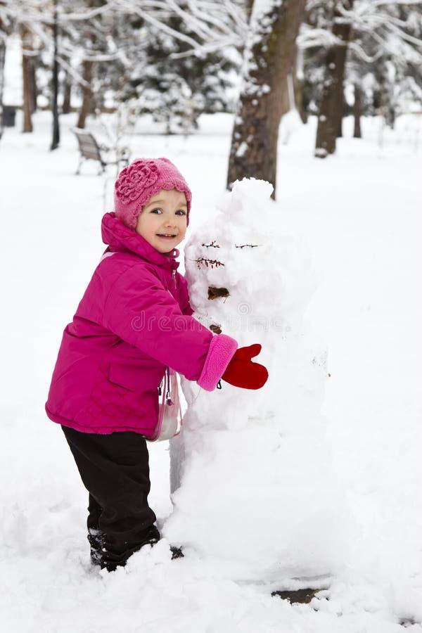 Menina que guardara um boneco de neve fotografia de stock