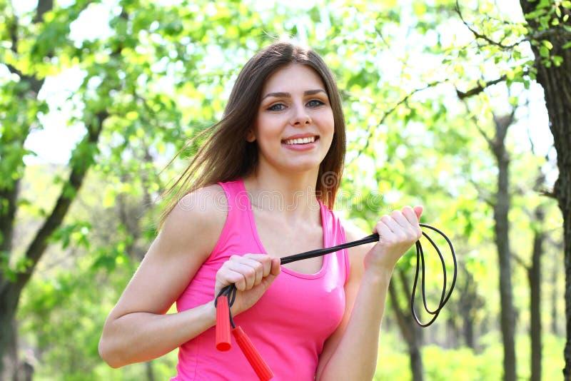 Menina que guardara uma corda de salto em um parque do verão imagem de stock
