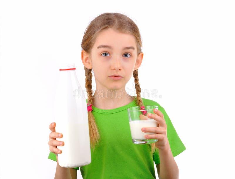 Menina que guardara uma garrafa e um vidro do leite fotos de stock royalty free