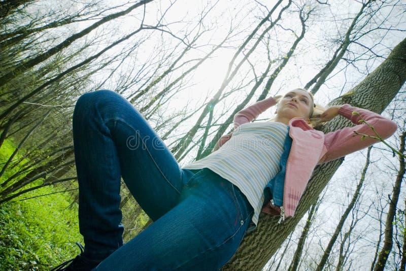 Menina que inclina-se de encontro a uma árvore imagens de stock
