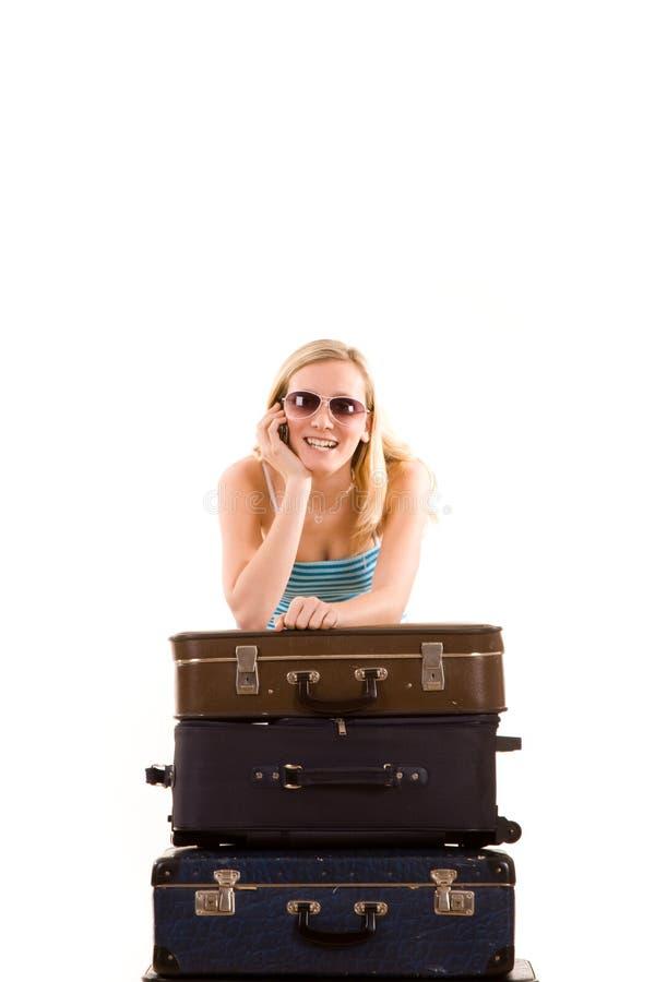 Menina que inclina-se em malas de viagem