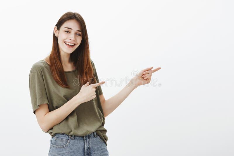 Menina que introduz seu melhor amigo ao irmão Estudante fêmea popular atrativo satisfeito, apontando certo com índice imagem de stock