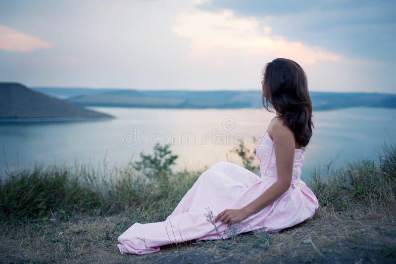 Menina que isitting no banco do rio e que olha o por do sol foto de stock