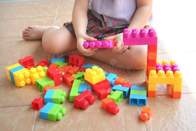 Menina que joga blocos do brinquedo imagem de stock