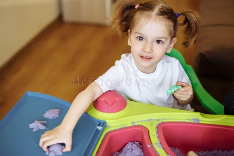 Menina que joga com areia cinética em casa, jogos, educação, crianças fotografia de stock