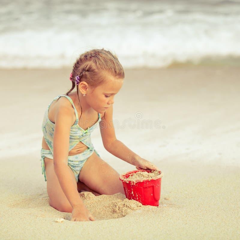 A menina que joga com areia dos brinquedos ajustou-se na praia fotos de stock