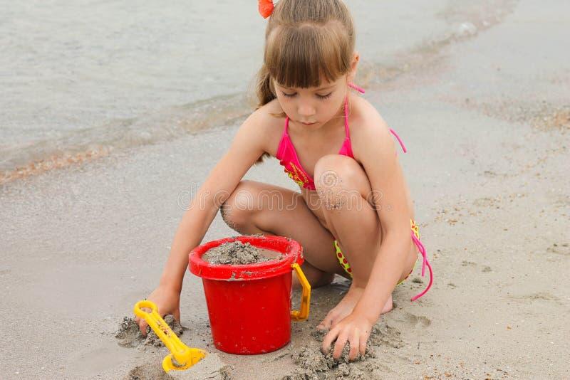 Menina que joga com a areia na costa de mar fotos de stock royalty free