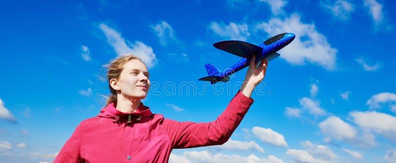 Menina que joga com avião Fundo do céu azul Conceito do curso e das férias foto de stock royalty free