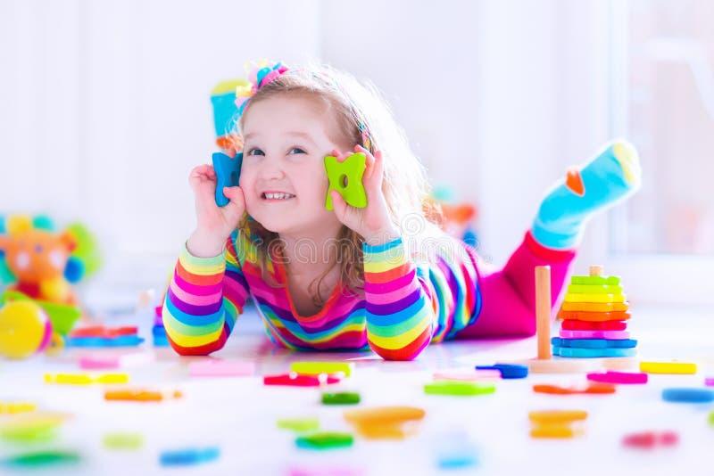 Menina que joga com blocos de madeira do brinquedo fotos de stock royalty free