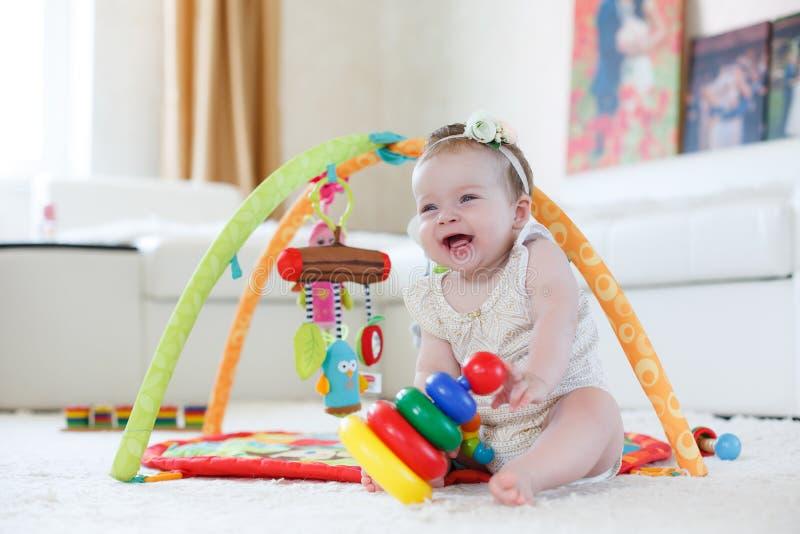 Menina que joga com brinquedos em casa no assoalho fotos de stock