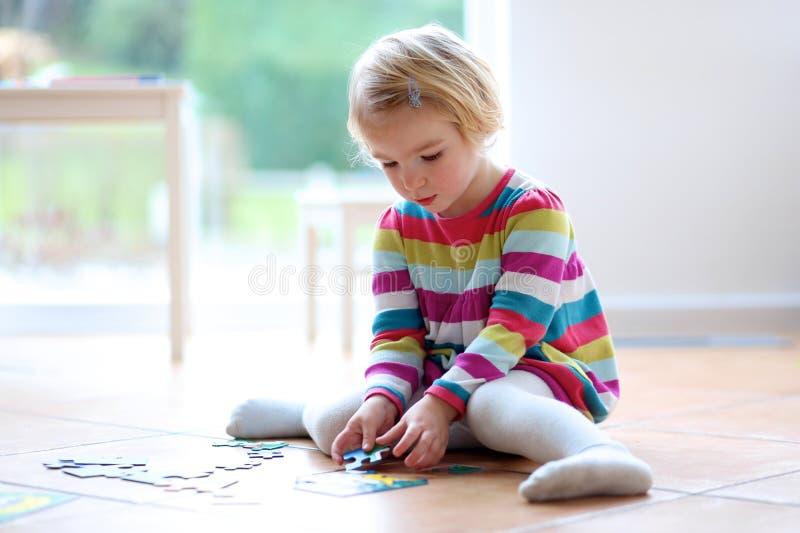 Menina que joga com enigma de serra de vaivém fotografia de stock