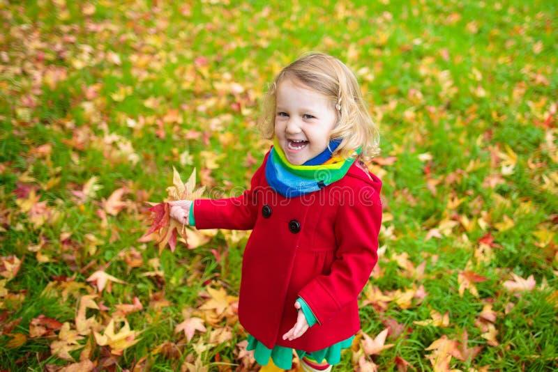 Menina que joga com a folha de bordo no outono imagem de stock