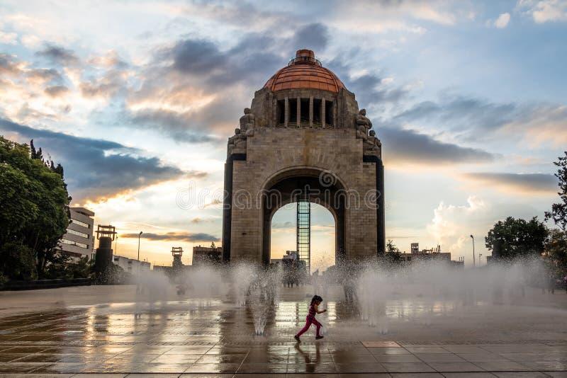 Menina que joga com a fonte de água na frente do monumento à revolução mexicana - Cidade do México, México fotografia de stock