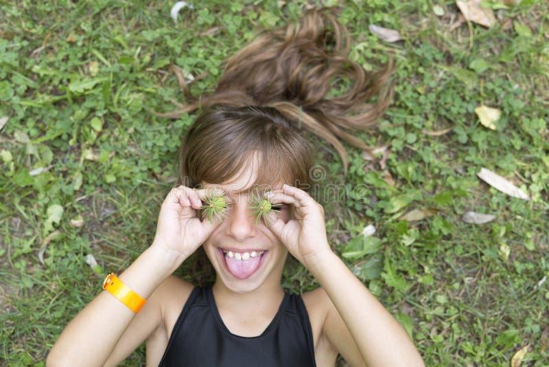 Menina que joga com a natureza de um parque imagem de stock royalty free