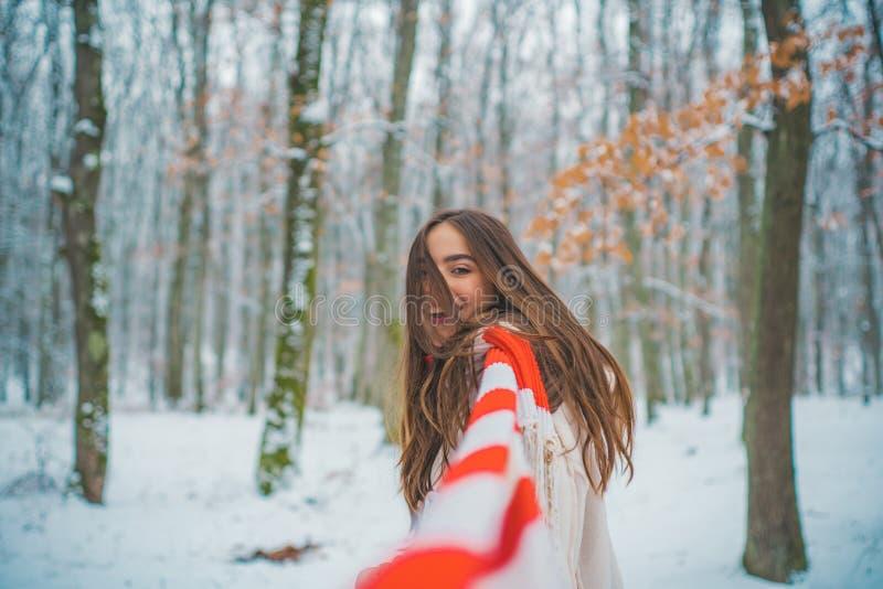 Menina que joga com neve no parque Mulheres na roupa do inverno O retrato de uma mulher bonita vestiu um revestimento fotografia de stock royalty free