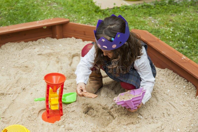 Menina que joga com os brinquedos da areia e do plástico em uma caixa de areia foto de stock