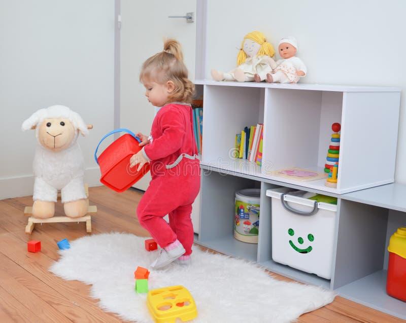 Menina que joga com os brinquedos na sala branca do ` s das crianças imagens de stock