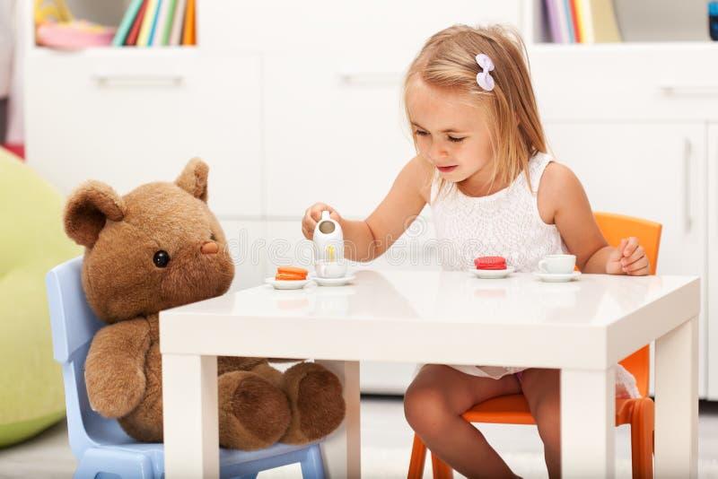 Menina que joga com seu urso do brinquedo - tendo um tea party imagens de stock royalty free