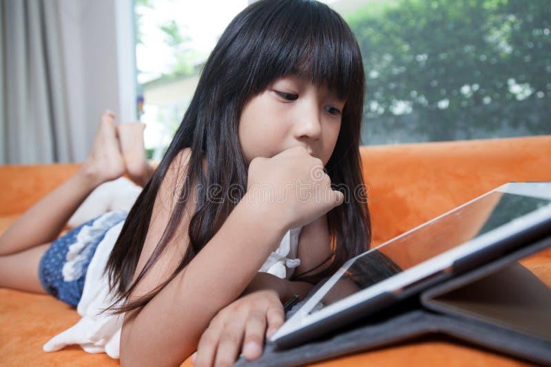 Menina que joga com tabuleta fotos de stock