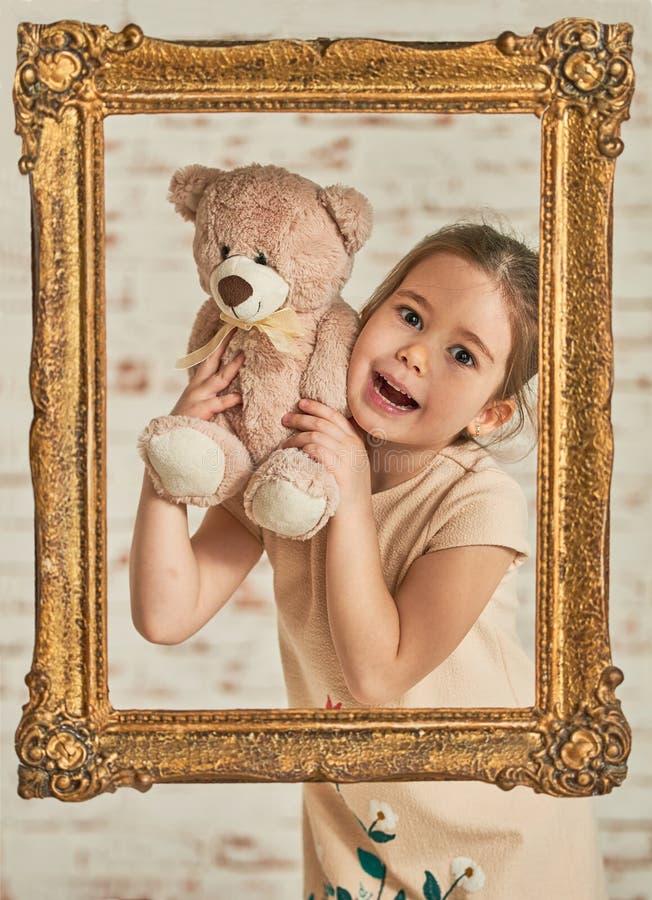 Menina que joga com urso de peluche fotos de stock royalty free