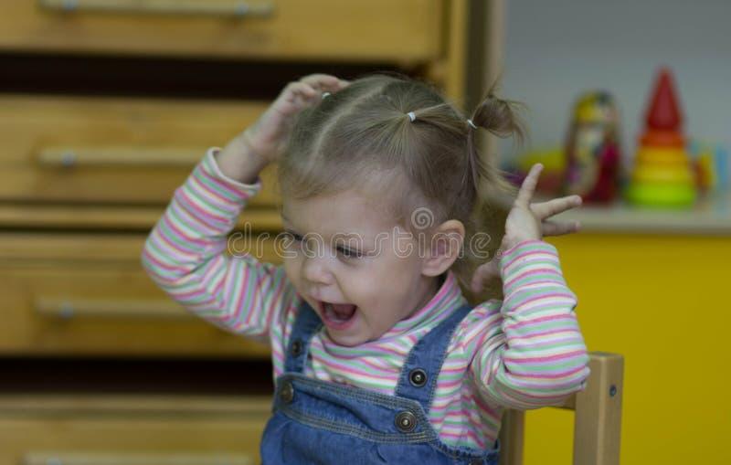 Menina que joga e que estuda em lições no jardim de infância foto de stock royalty free