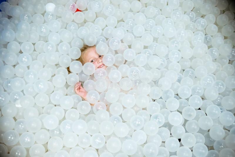 A menina que joga e tem o divertimento na associação seca com bolas brancas A criança está feliz em uma associação com bolas Rapa imagem de stock royalty free