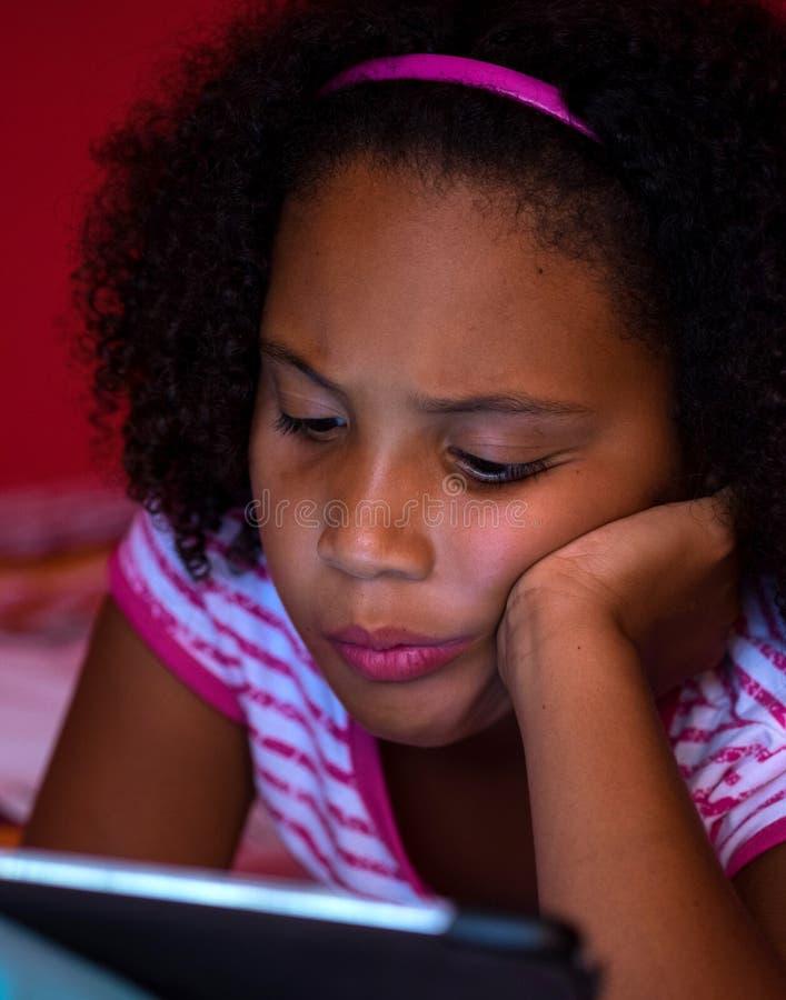 Menina que joga em sua tabuleta foto de stock