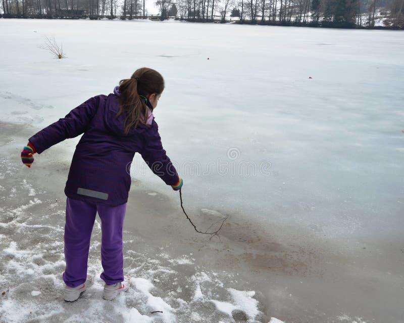 Menina que joga em um lago congelado foto de stock royalty free