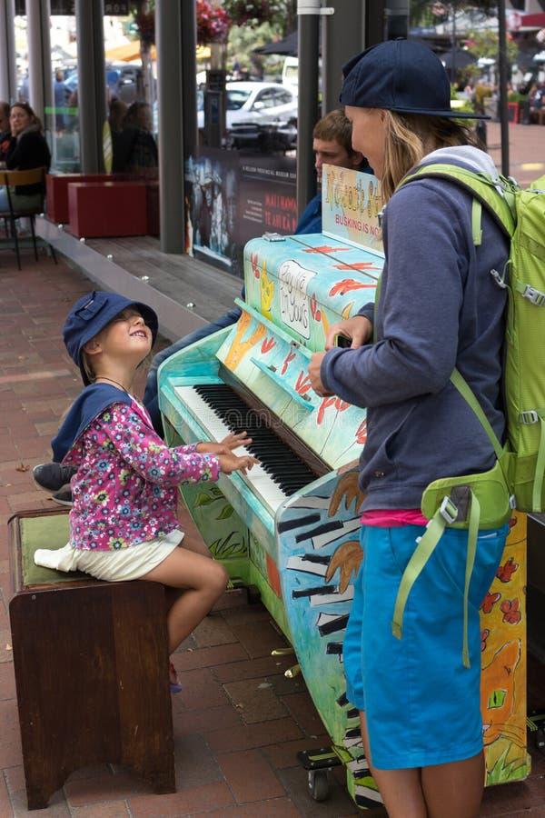 Menina que joga em um piano da rua fotografia de stock royalty free