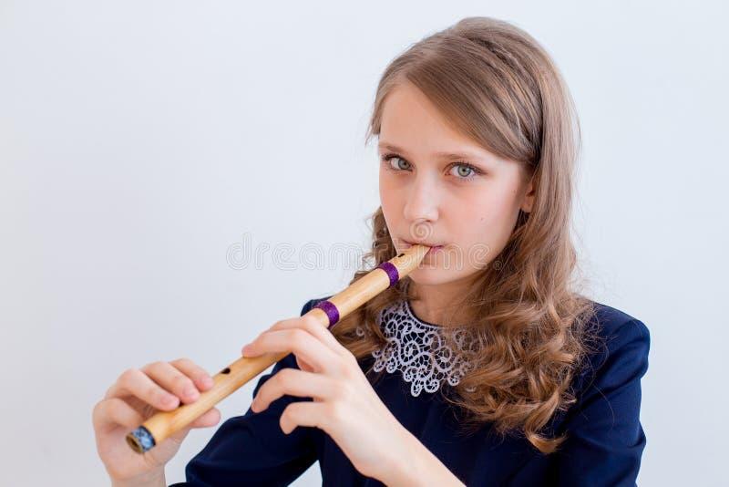 Menina que joga em uma flauta foto de stock royalty free
